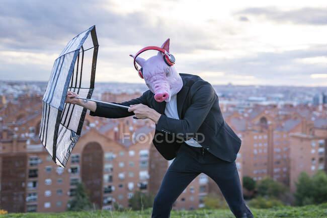 Чоловічий підприємець у масці свині та бездротових навушниках, що борються з парасолькою на небі. — стокове фото