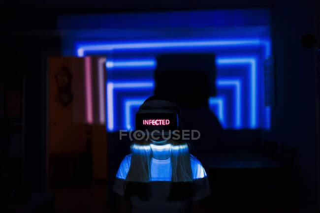 Mujer con gafas de realidad virtual con texto infectado en casa durante pandemia - foto de stock