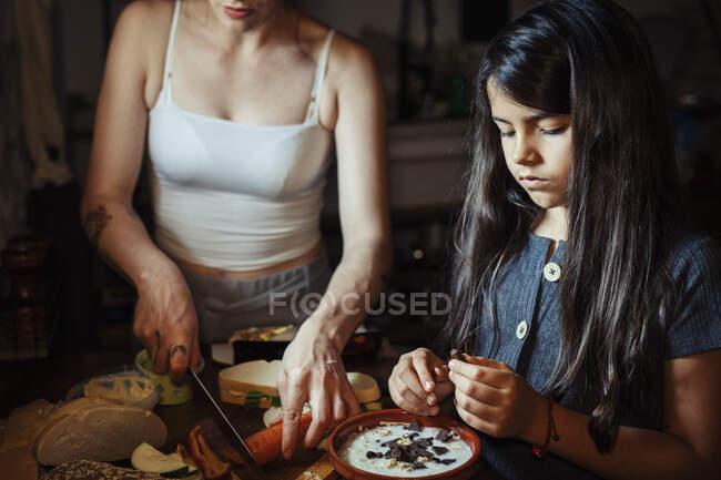 Мать и дочь готовят завтрак, стоя дома на кухне — стоковое фото