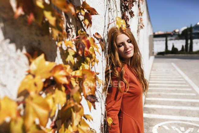 Mujer joven en vestido rojo con los ojos cerrados de pie contra la pared de hiedra - foto de stock