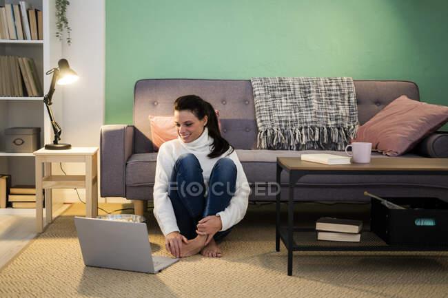 Доросла жінка користується ноутбуком, сидячи вдома на підлозі. — стокове фото