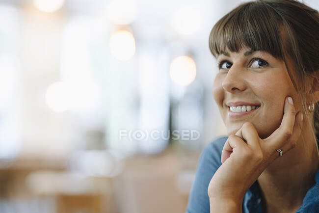 Smiling female entrepreneur looking away with hand on chin sitting in cafe — Stock Photo