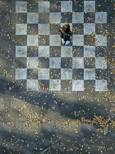 Mujer de pie sobre tablero de ajedrez pintado sobre asfalto - foto de stock