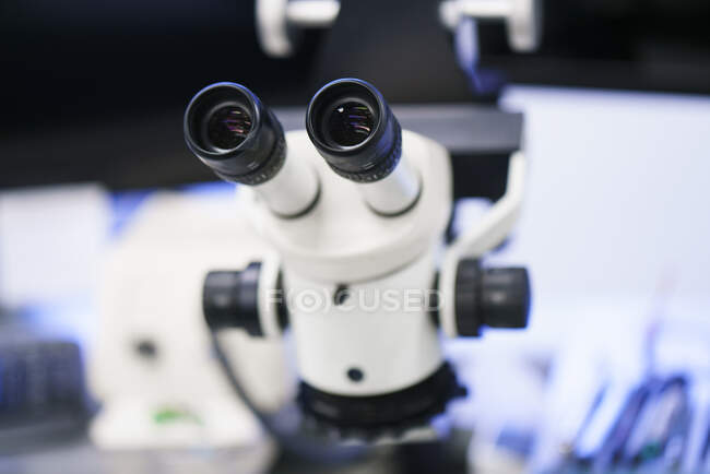 Gros plan du microscope blanc au laboratoire éclairé — Photo de stock