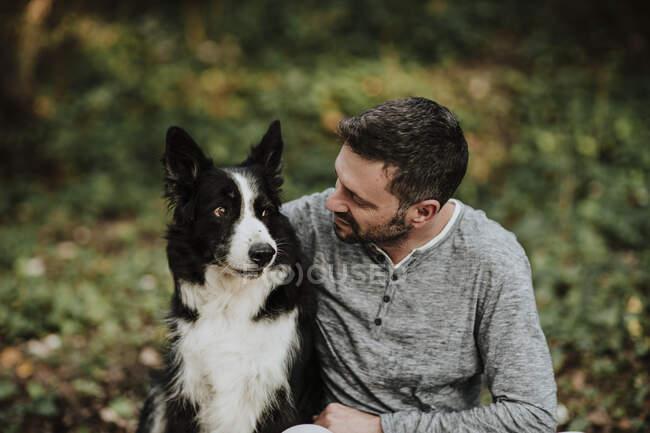 Hombre sentado con perro en el parque público - foto de stock