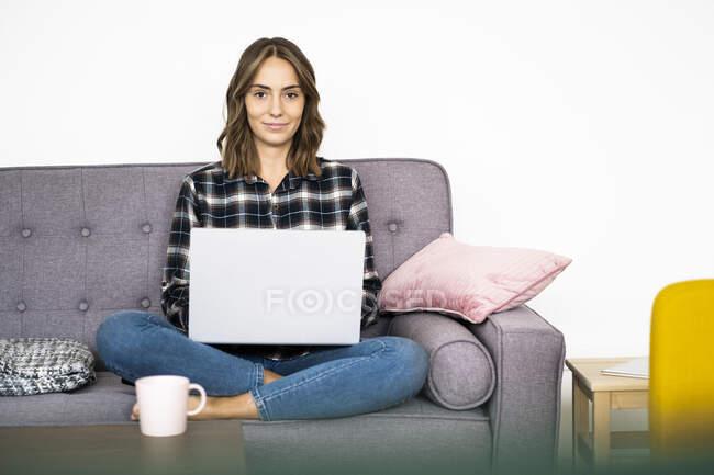 Улыбающаяся молодая женщина, работающая на ноутбуке, сидя дома на диване — стоковое фото