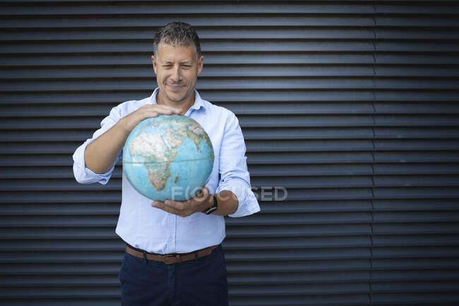 Бізнесмен тримає глобус, стоячи навпроти металевої стіни. — стокове фото