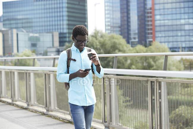 Hombre usando el teléfono inteligente mientras sostiene la taza de café desechable caminando por el sendero en la ciudad - foto de stock