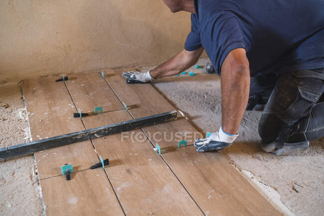 Sección media del hombre maduro que pone el suelo de parquet en casa - foto de stock