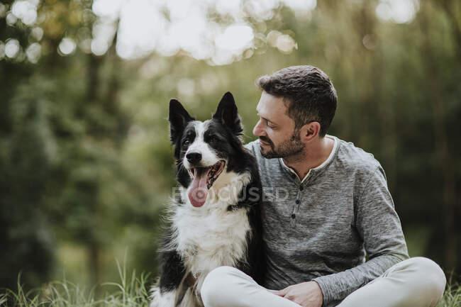 Hombre sonriente mirando al perro mientras está sentado en el parque público - foto de stock