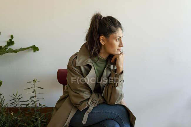 Modelo feminino pensativo com a mão no queixo sentado contra a parede em casa — Fotografia de Stock