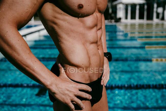 Nadador masculino con músculos abdominales parado junto a la piscina en un día soleado - foto de stock