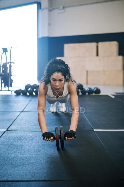 Atleta haciendo ejercicio con rueda de tonificación abdominal en el gimnasio - foto de stock