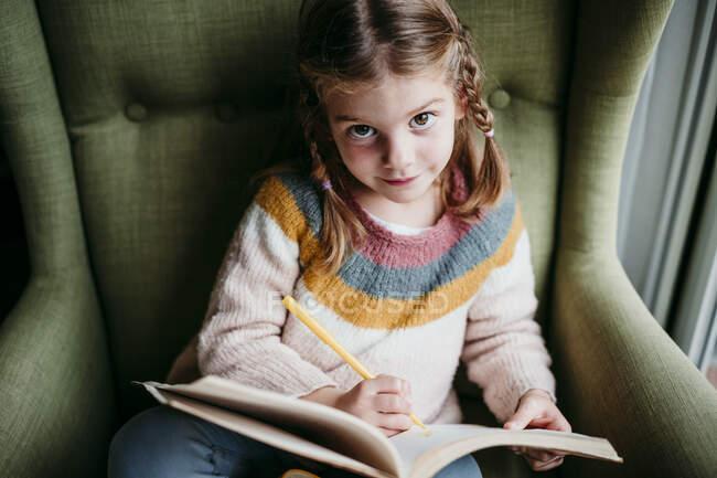 Милая девушка делает домашнее задание, сидя на стуле дома — стоковое фото