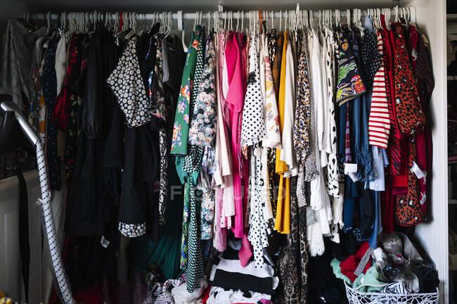 Variação de roupas femininas penduradas no rack de roupas no guarda-roupa no apartamento — Fotografia de Stock