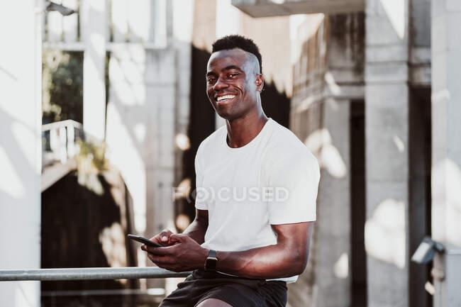 Atleta di sesso maschile utilizzando smartphone guardando lontano mentre seduto — Foto stock