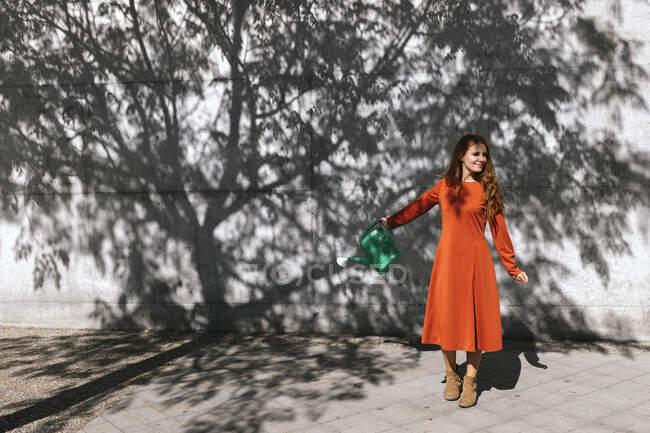 Jovem mulher molhando sombra de árvore enquanto está de pé contra a parede — Fotografia de Stock