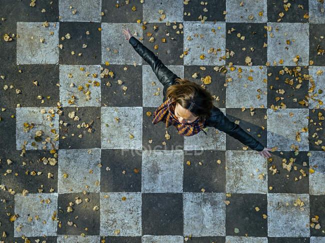 Беззаботная женщина, вращающаяся на асфальте, раскрашенная с проверенным рисунком — стоковое фото