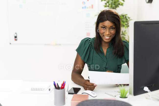 Smiling businesswoman holding paper while sitting by desk at office — Stock Photo