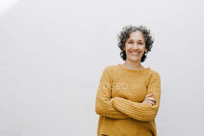 Усміхнена жінка в оранжевому светрі стоїть зі схрещеними руками на білій стіні. — стокове фото
