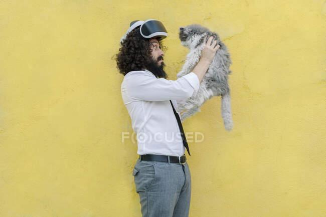 Людина з віртуальними окулярами на голові, граючи з котом, стоячи проти стіни. — стокове фото