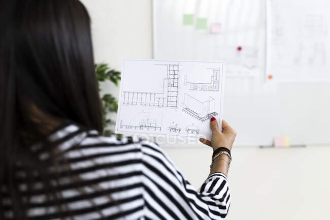 Female architect analyzing floor plan on paper at creative workplace — Stock Photo