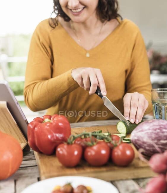 Mujer sonriente cortando vegetales mientras está de pie junto a la mesa en casa - foto de stock
