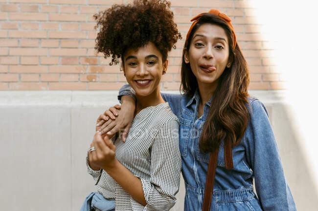 Giovane donna attaccare lingua fuori mentre in piedi con un amico contro il muro — Foto stock