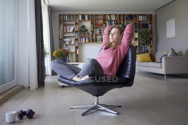 Жінка з руками позаду голови розслаблює крісло вдома. — стокове фото