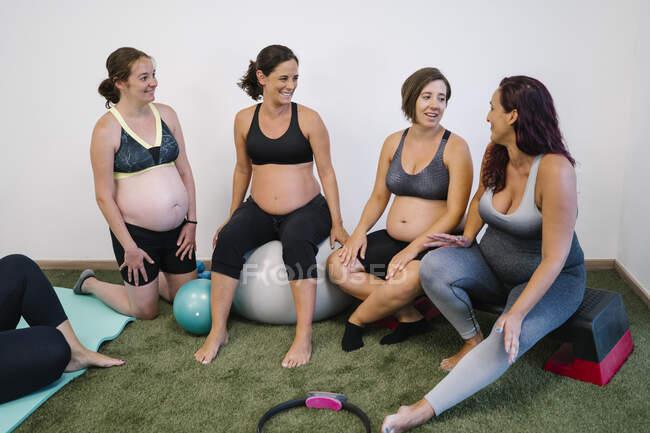 Беременные женщины разговаривают друг с другом в студии йоги — стоковое фото