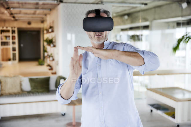 Male businessman wearing virtual reality headset gesturing while standing at home — Stock Photo