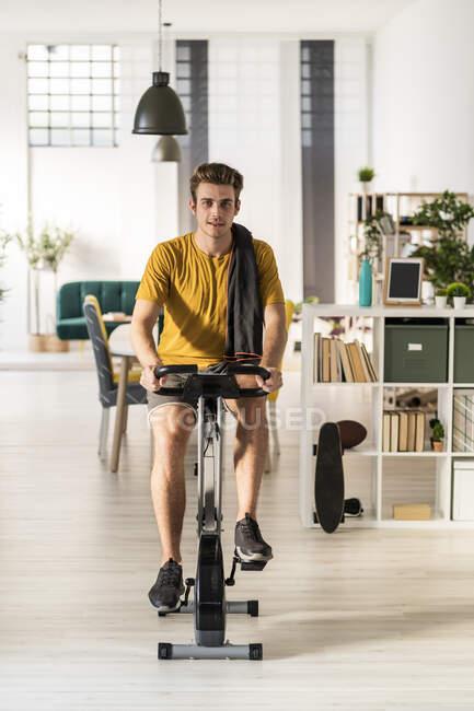 Молодой человек катается на велосипеде на тренажерах дома — стоковое фото