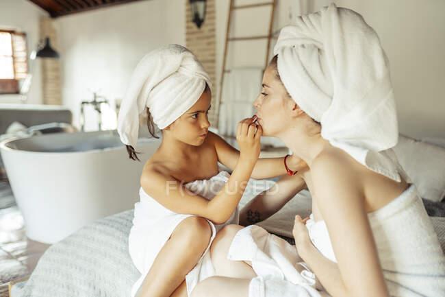 Chica en toalla concentrándose mientras se aplica lápiz labial en los labios de la mujer en casa - foto de stock