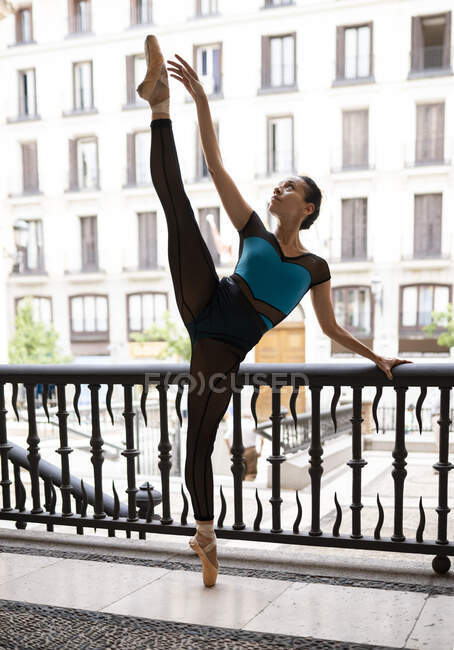 Танцующая балетная танцовщица стоит у ограждения в городе — стоковое фото