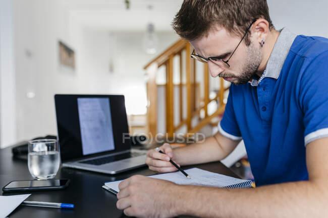 Jeune étudiant dédié à l'université qui fait des mathématiques à la maison — Photo de stock