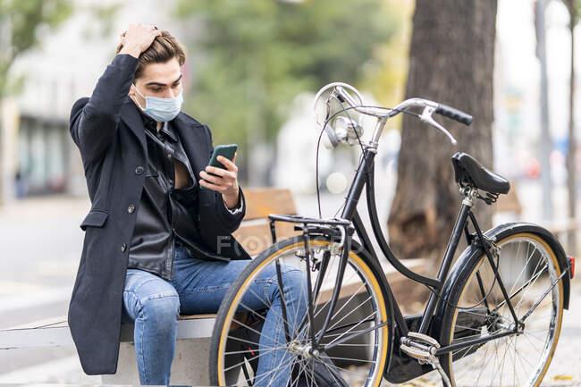 Молодий чоловік у волоссі з використанням смартфона під час сидіння на лавці на велосипеді в місті під час COVID-19. — стокове фото