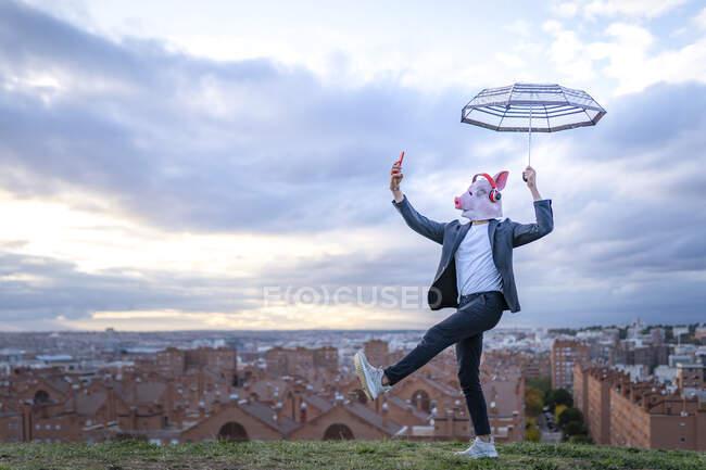 Чоловічий підприємець у масці зі свинячою маскою, що тримає парасольку під час заходу сонця. — стокове фото