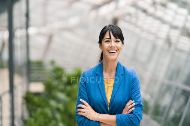 Happy businesswoman with arms crossed in office — Stock Photo