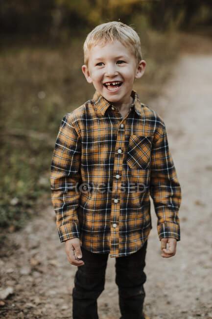 Улыбающийся мальчик в клетчатой рубашке стоит на тропинке в лесу — стоковое фото
