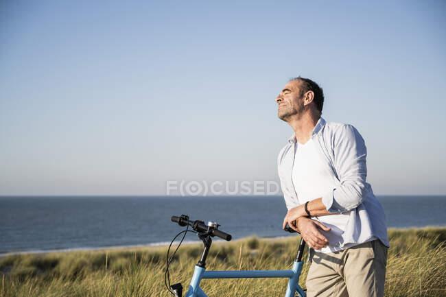 Hombre con los ojos cerrados apoyado en bicicleta en la playa contra el cielo despejado - foto de stock