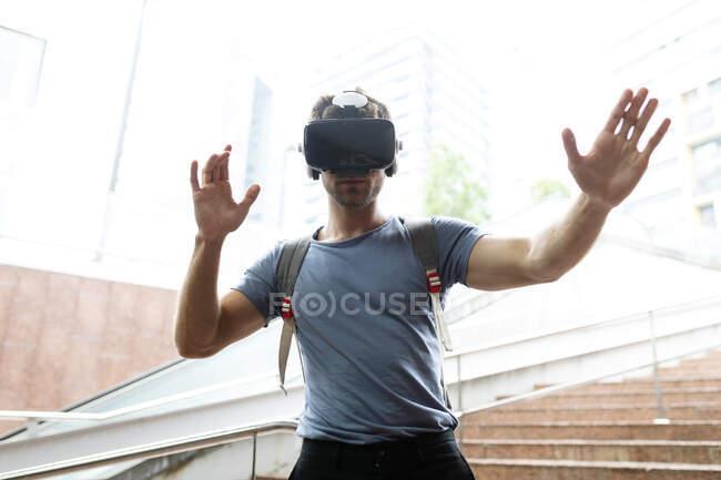 Young man enjoying virtual reality headset at subway station — Stock Photo