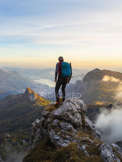 Senderista pensativo con mochila de pie en el pico de la montaña durante el amanecer en los Alpes bergamascos, Italia - foto de stock