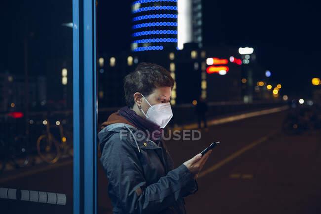 Mujer madura que usa mascarilla protectora usando teléfono móvil mientras está parada de autobús en la ciudad - foto de stock