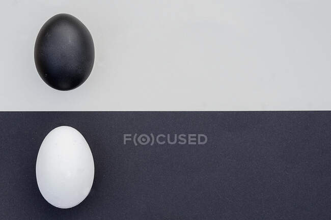 Studio shot of black and white eggs on contrasting backgrounds — Stock Photo