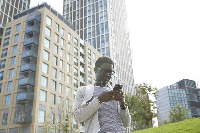 Profesional masculino usando teléfono móvil mientras está parado contra el edificio de oficinas en el centro de la ciudad - foto de stock