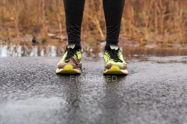 Low section of man standing on road during rainy season — Stock Photo