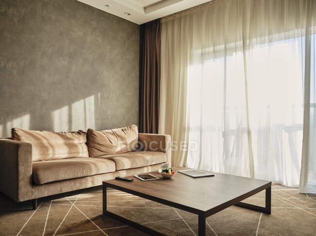 Mesa de centro de madera con sofá vacío en habitación de hotel de lujo - foto de stock
