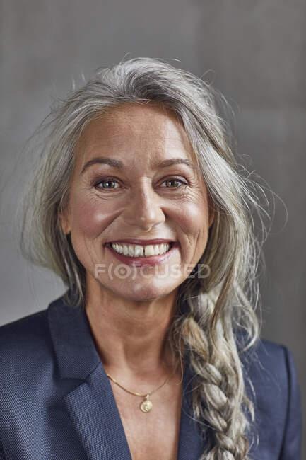 Heureuse femme d'affaires avec les cheveux gris contre le mur au bureau à la maison — Photo de stock