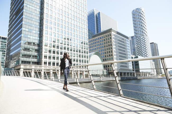 Profesional femenina en llamada telefónica caminando en el puente durante el día soleado - foto de stock
