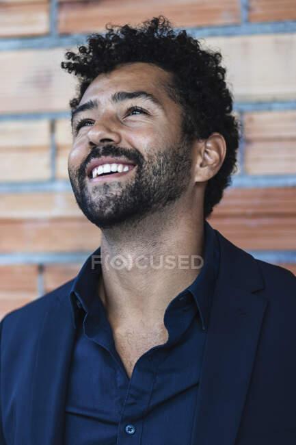 Fiducioso imprenditore sorridente in tuta in piedi contro il muro — Foto stock